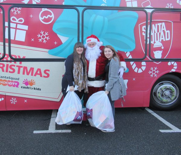 Becca and Eve delivering toys to Santa for Radio City Cash for Kids Appeal